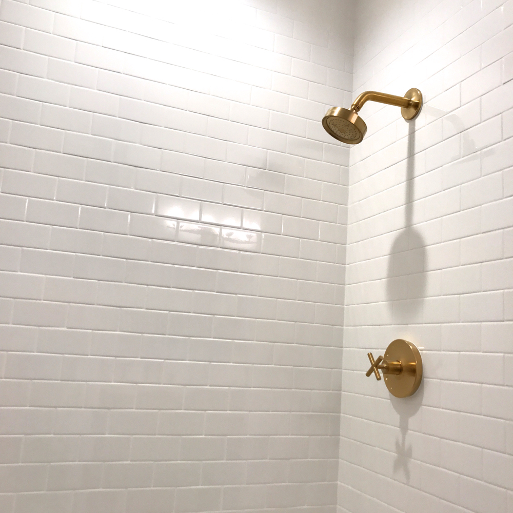 brushed gold shower head kohler vibrant moderne subway tile